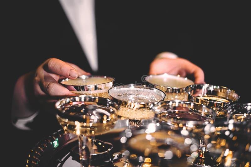A mão do homem que guarda vidros dourados brilhantes do champanhe em uma sala escura foto de stock