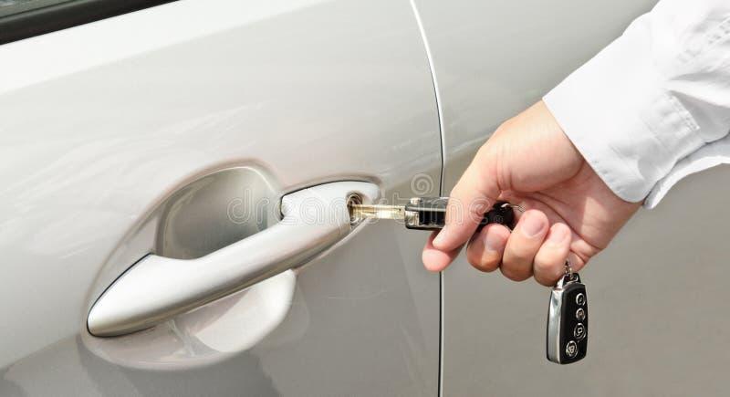 A mão do homem que introduz uma chave na fechadura da porta de um carro fotografia de stock