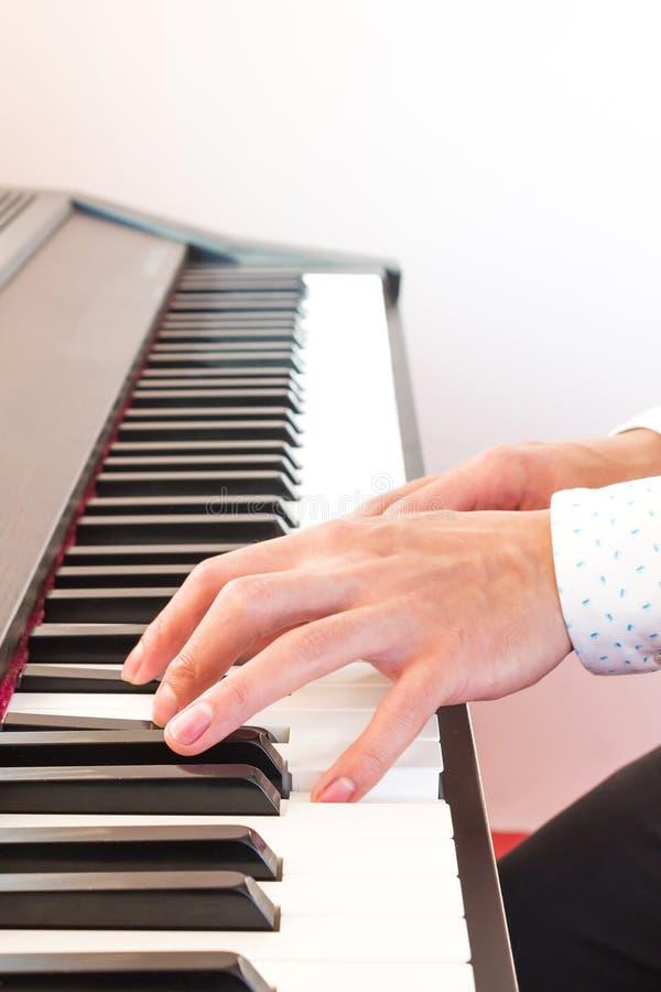 A mão do homem que joga o piano fotos de stock