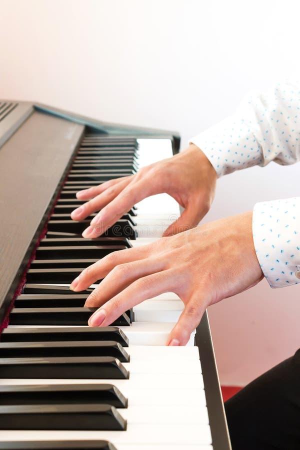 A mão do homem que joga o piano foto de stock