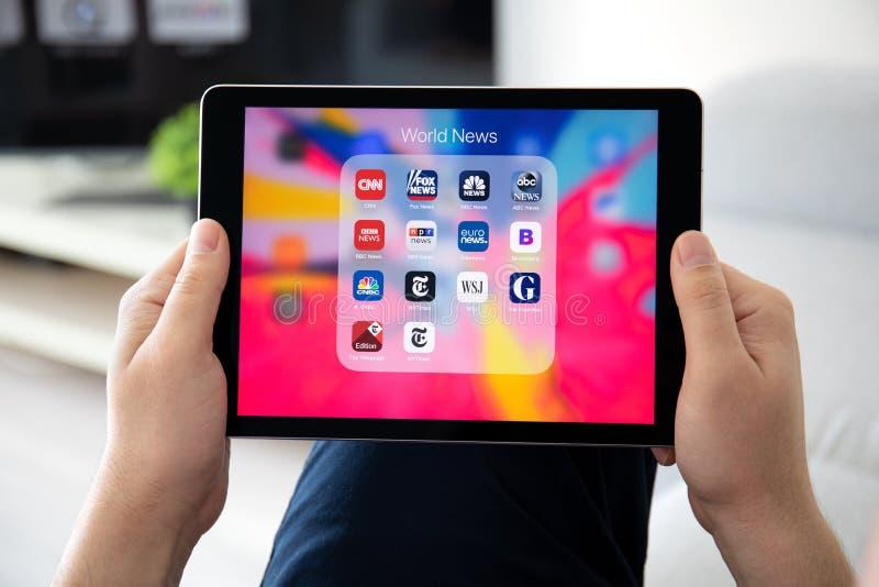Mão do homem que mantém o iPad pro com aplicações populares da notícia fotografia de stock