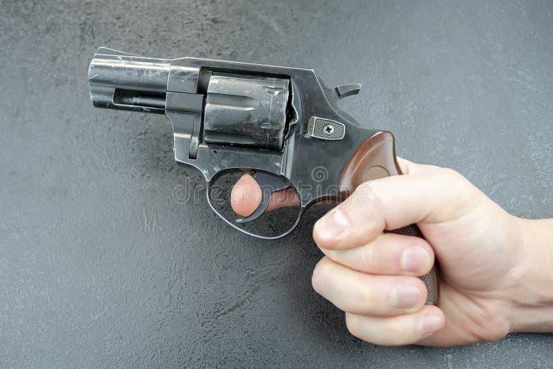 A mão do homem que mantém um revólver contra um fundo cinzento, dedo no disparador fotos de stock