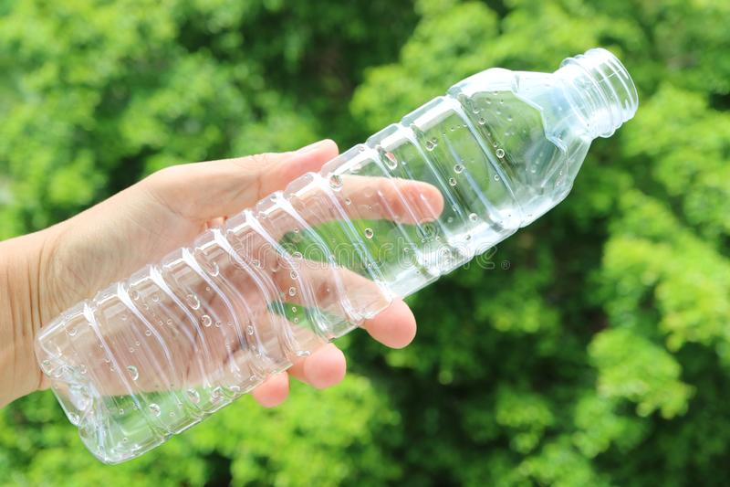 A mão do homem que mantém uma garrafa plástica vazia da água potável contra a folha verde obscura imagens de stock royalty free