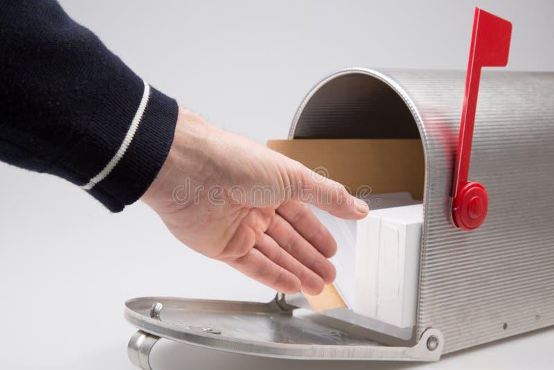 Mão do homem que põe o pacote e o correio em entregar a caixa postal do postmail fotografia de stock royalty free