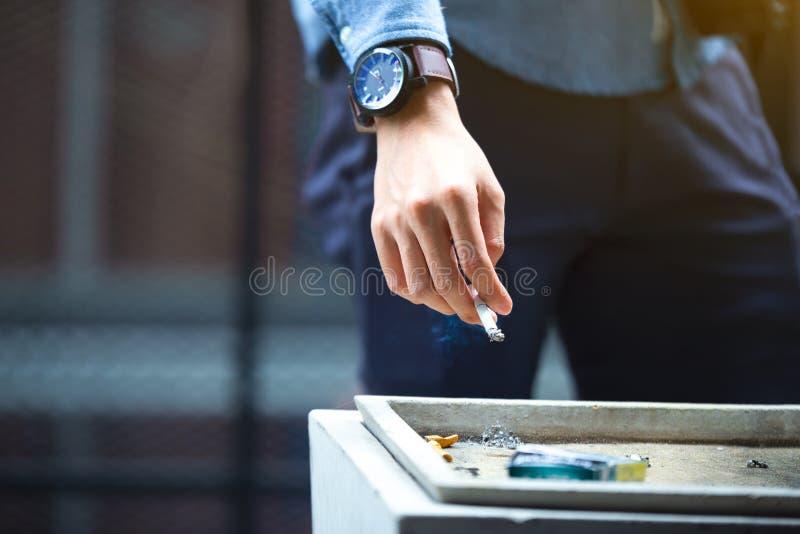 Mão do homem que põe para fora o cigarro sobre o cinzeiro da rua, cigarro fotografia de stock royalty free