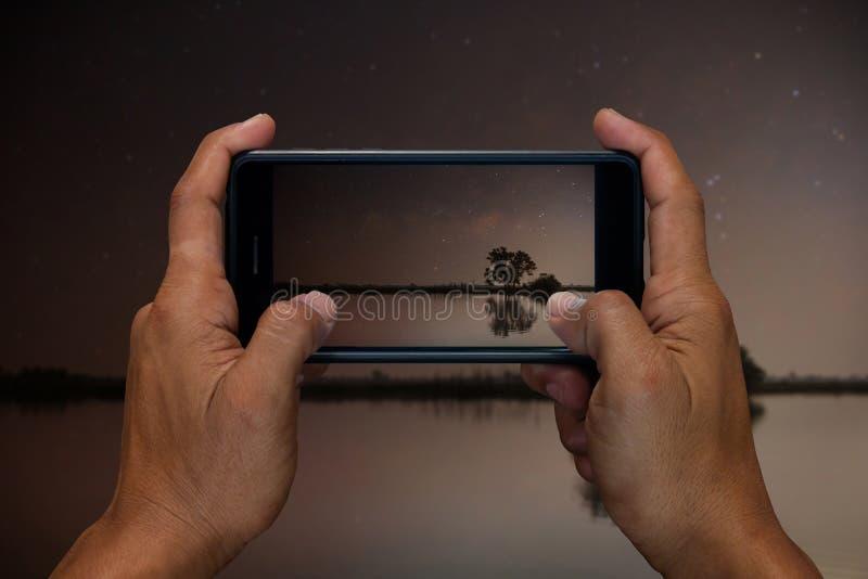 A mão do homem que realiza e que usa o móbil, o telefone celular, a fotografia esperta do telefone e o lago na noite com protagon fotografia de stock