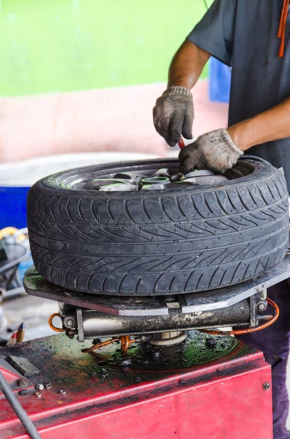 Mão do homem que remove o pneu de carro imagem de stock