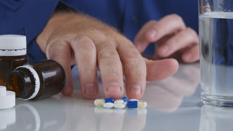 Mão do homem que toma comprimidos da tabela para um tratamento médico imagem de stock