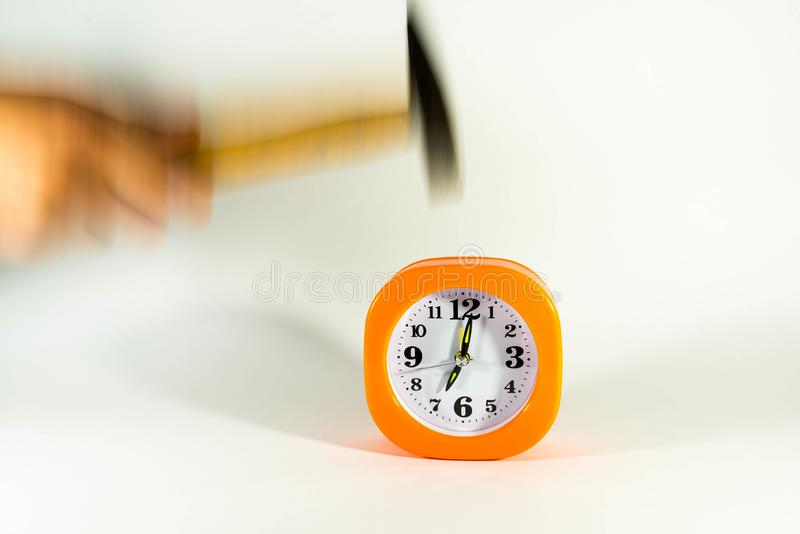 A mão do homem quebra o despertador com um martelo, foto de stock