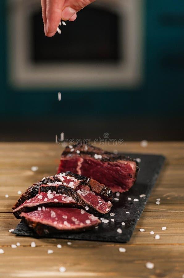 A mão do homem salgada sobre a carne fritada cortada fotos de stock