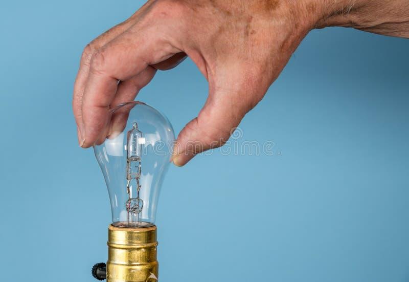 Mão do homem superior que desaparafusa o bulbo de halogênio imagem de stock royalty free
