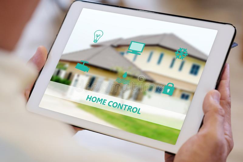 Mão do homem superior usando a tabuleta digital com ícone esperto do controle da casa na tela ao sentar-se no sofá em casa, contr fotografia de stock
