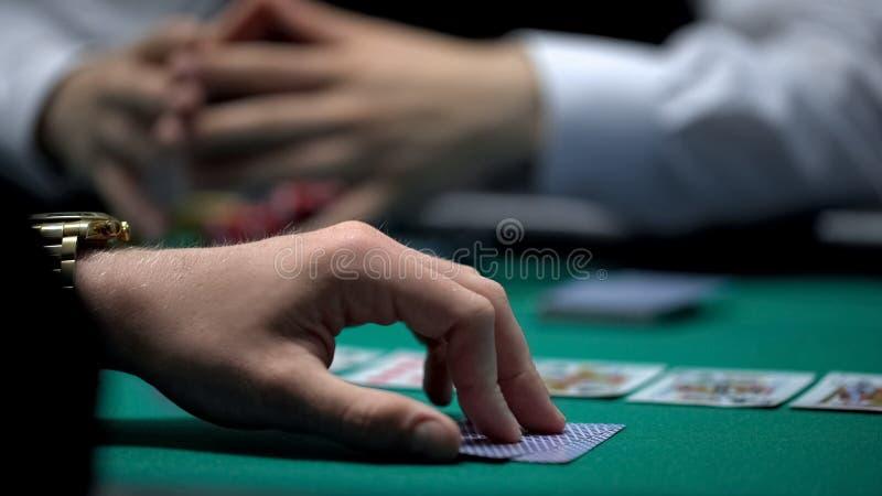 Mão do jogador do casino pronta para verificar a combinação do cartão do pôquer, jogo de dedicação fotografia de stock