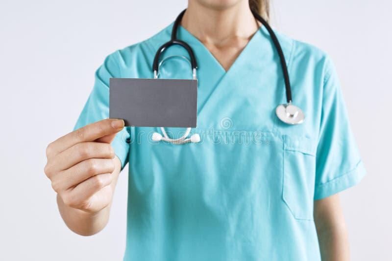 Mão do médico da mulher que guarda um cartão vazio no fundo cinzento imagens de stock royalty free