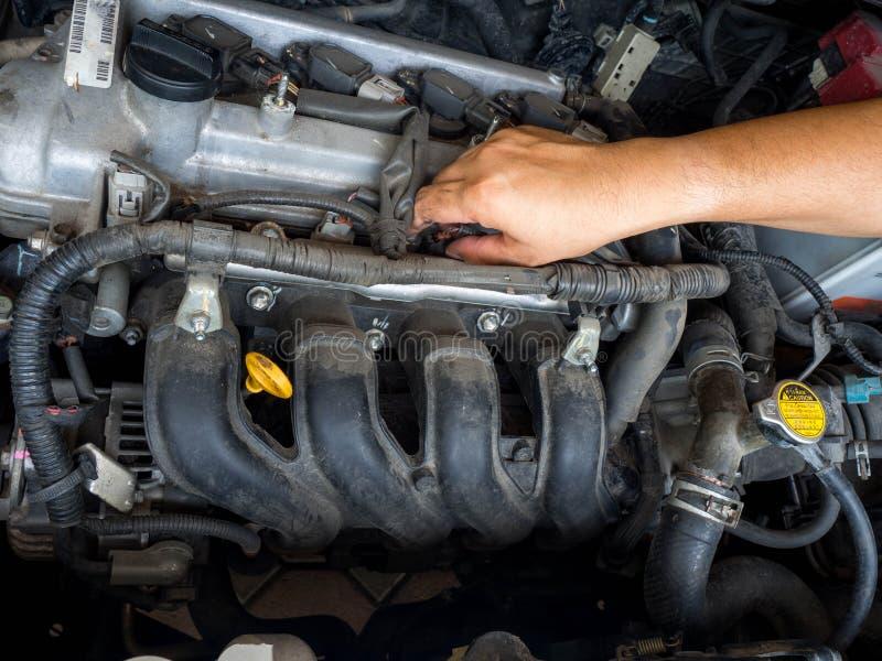 Mão do mecânico de carro que trabalha no serviço de reparação de automóveis Tem o motor de automóveis velho do reparo listado com imagem de stock royalty free