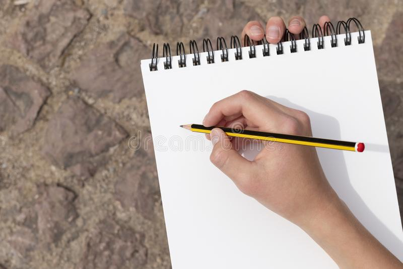 A mão do menino com um lápis sobre um bloco de notas aberto no parque fotografia de stock royalty free