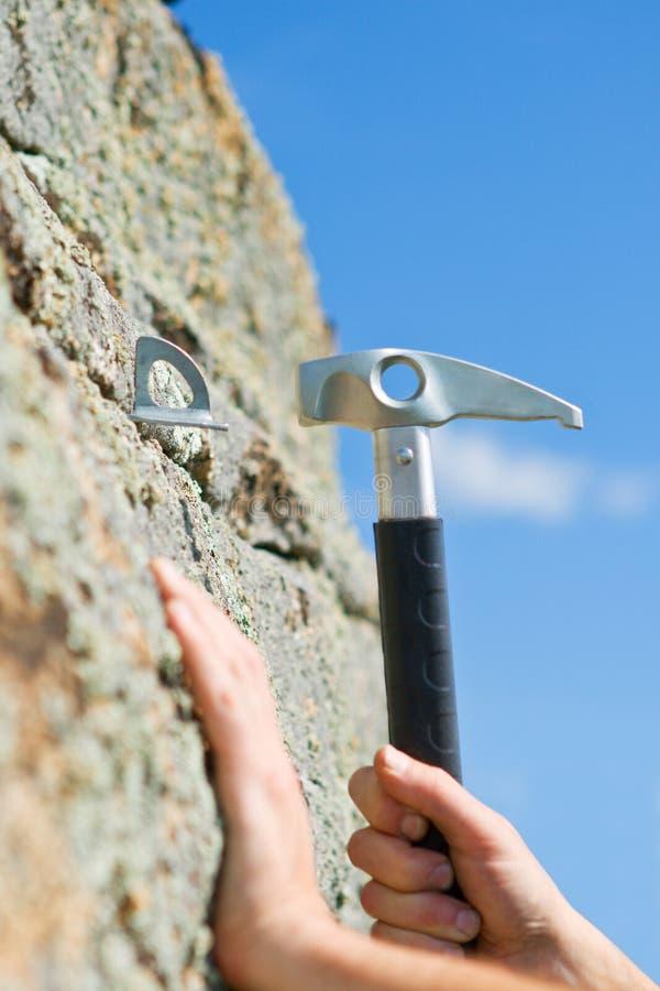 Mão do montanhista e do martelo fotografia de stock