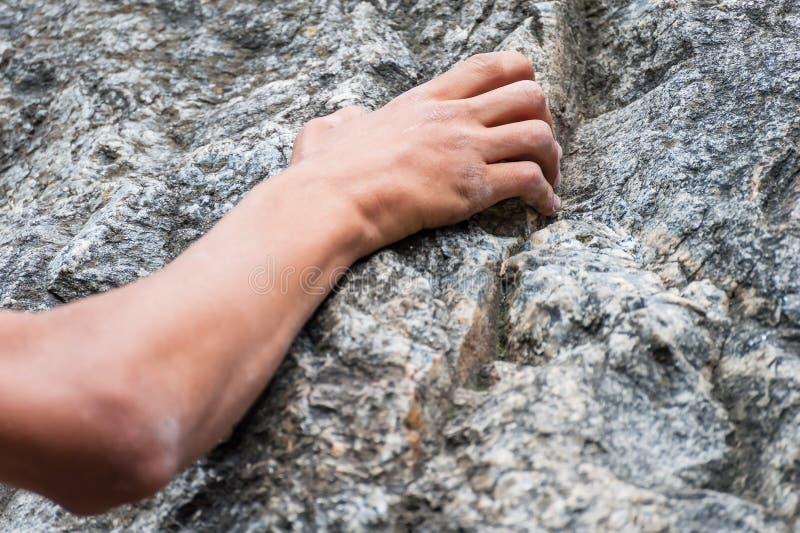 A mão do montanhista que guarda uma rocha fotos de stock royalty free