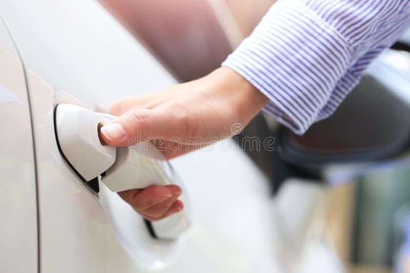 Mão do negócio no punho Fêmea do close-up que abre uma porta de carro imagens de stock