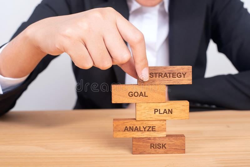 Mão do negócio que arranja o bloco de madeira com conceito da palavra ESTRATÉGIA foto de stock