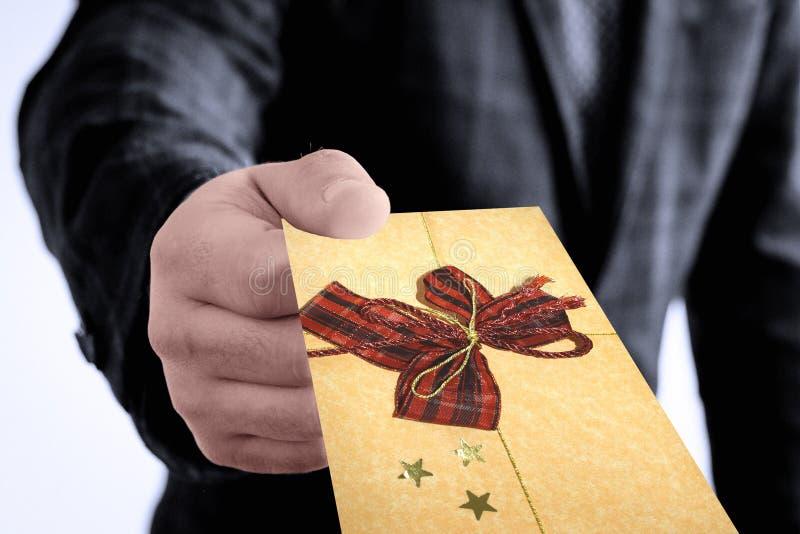 Mão do negócio que dá um envelope decorado do cartão de Natal foto de stock