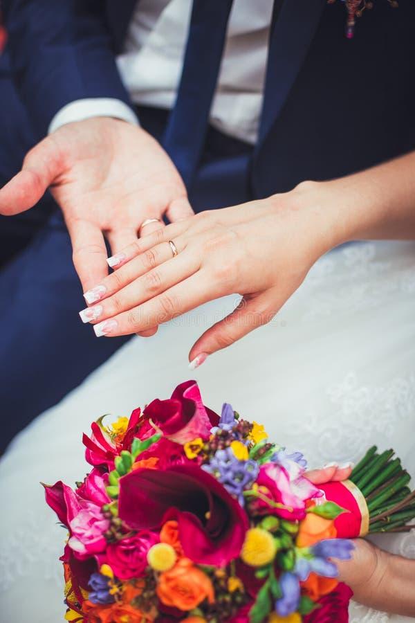 Mão do noivo e da noiva com alianças de casamento imagens de stock
