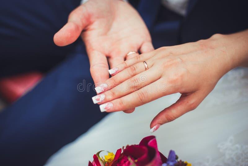 Mão do noivo e da noiva com alianças de casamento imagem de stock
