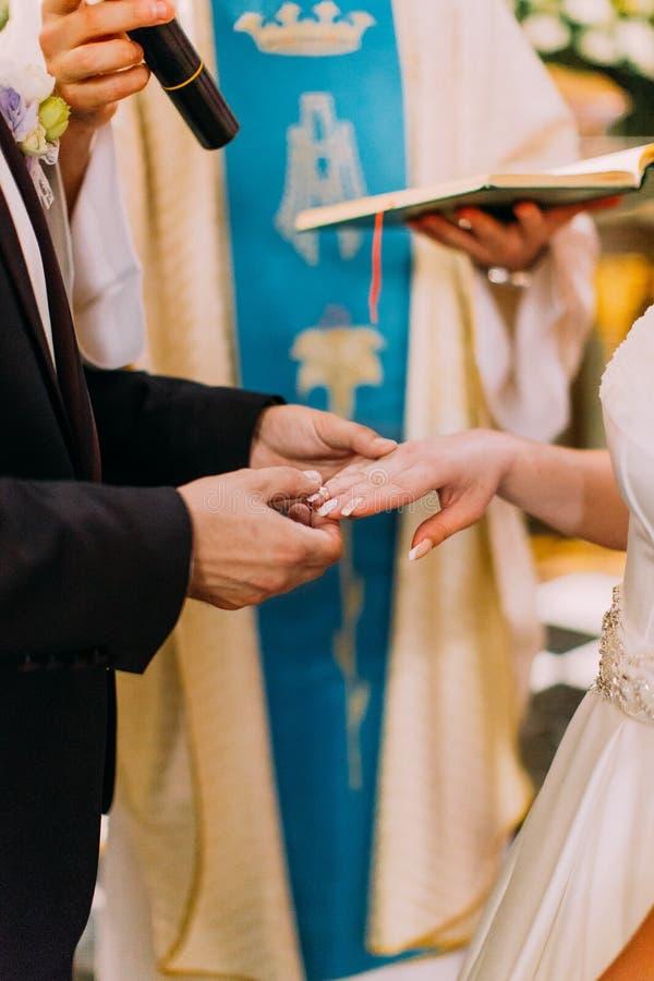 A mão do noivo está pondo a aliança de casamento sobre o dedo da noiva imagem de stock royalty free