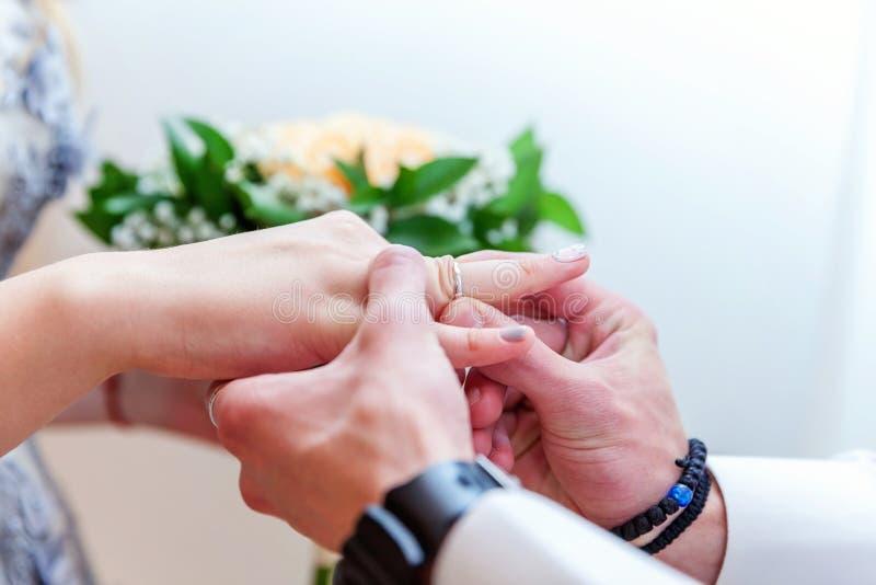 Mão do noivo que põe a aliança de casamento sobre o dedo da noiva fotografia de stock