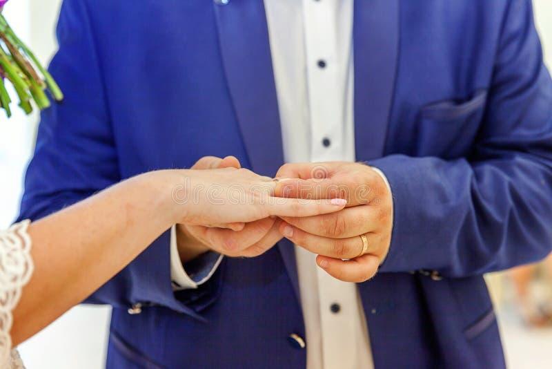 Mão do noivo que põe a aliança de casamento sobre o dedo da noiva imagens de stock royalty free