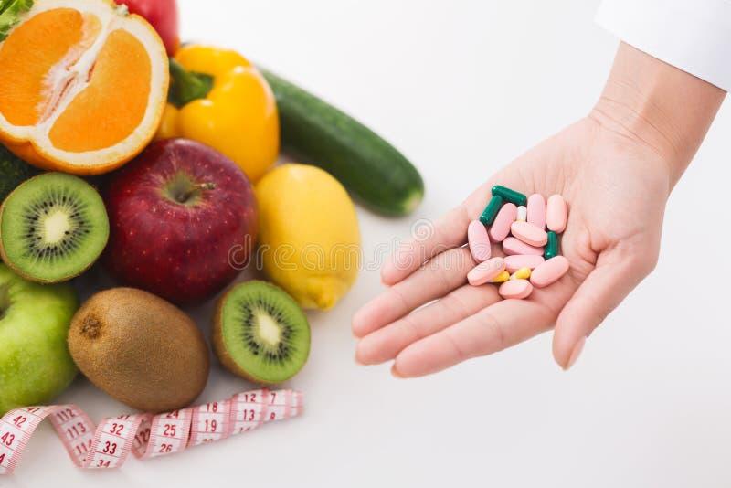 Mão do nutricionista com o montão dos comprimidos no local de trabalho fotos de stock