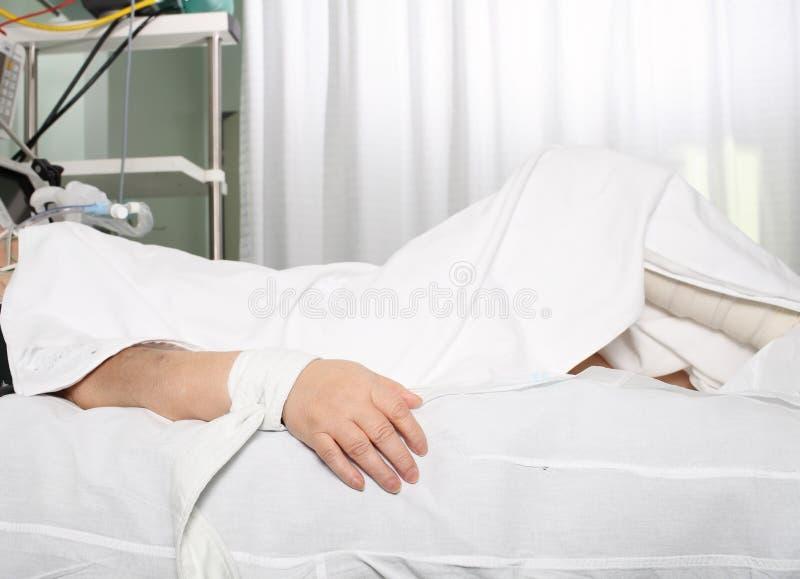 Mão do paciente de sofrimento amarrada à cama foto de stock