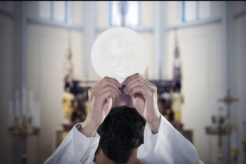 A mão do pastor aumenta um pão do comunhão na igreja foto de stock
