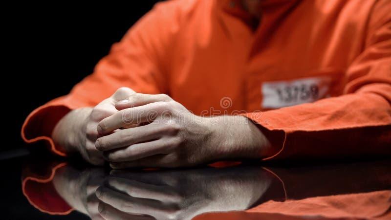 Mão do prisioneiro masculino, interno que dá a evidência na sala de detenção, cooperação imagens de stock