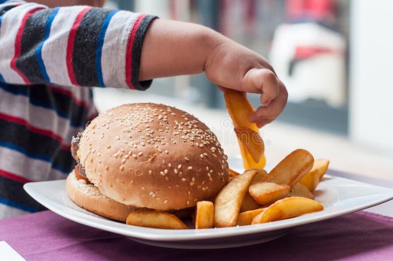 mão do rapaz pequeno que come o Hamburger e as batatas fritas em foto de stock