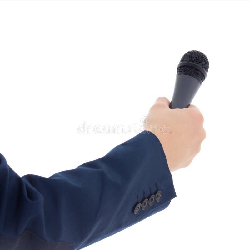 A mão do repórter que mantém um microfone isolado no branco imagem de stock