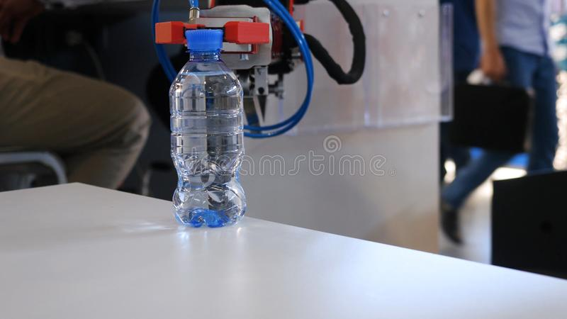 A mão do robô está guardando uma garrafa da água media Progresso tecnol?gico O braço robótico guarda uma garrafa de água foto de stock royalty free