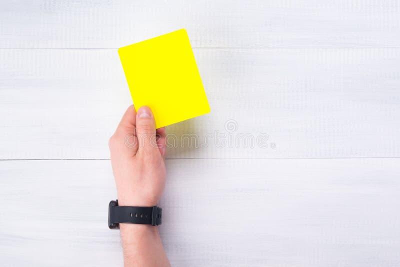 A mão do ` s do árbitro guarda um cartão amarelo da pena, em um fundo cinzento imagem de stock royalty free