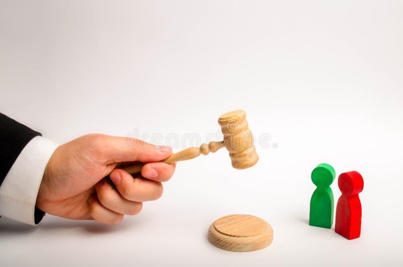 A mão do ` s do árbitro guarda um martelo e emite uma sentença na disputa entre os oponentes vermelhos e verdes casos em tribunal imagens de stock