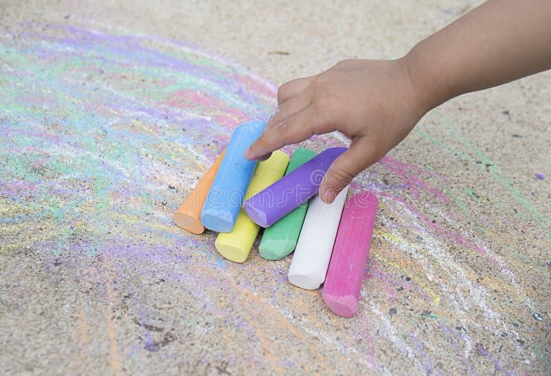 Mão do ` s da criança com giz colorido fotos de stock royalty free