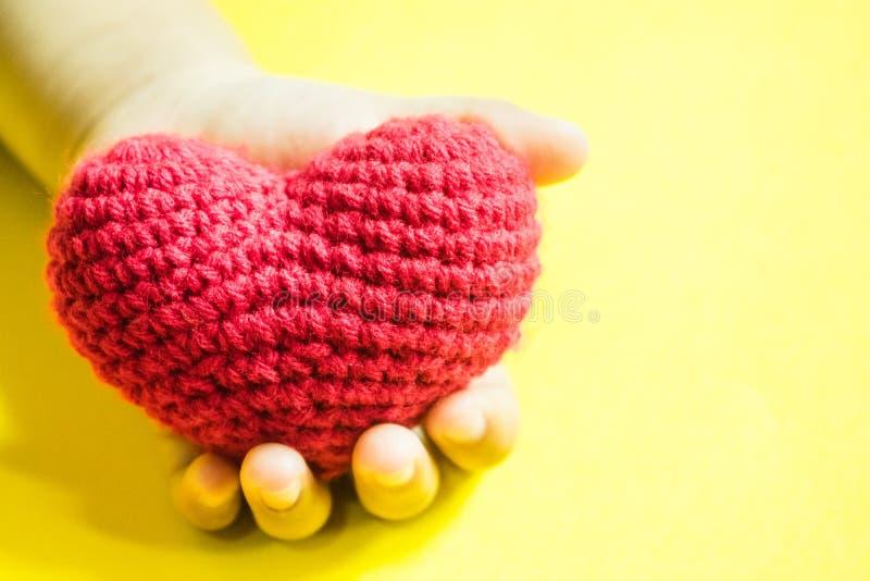 Mão do ` s da criança com um coração vermelho no fundo amarelo fotografia de stock royalty free