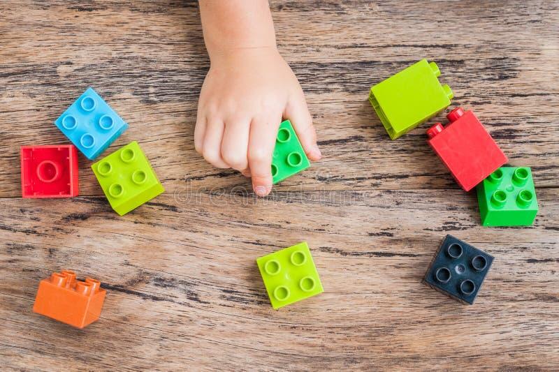 Mão do ` s da criança e cubos coloridos da construção do brinquedo Vista superior fotos de stock royalty free