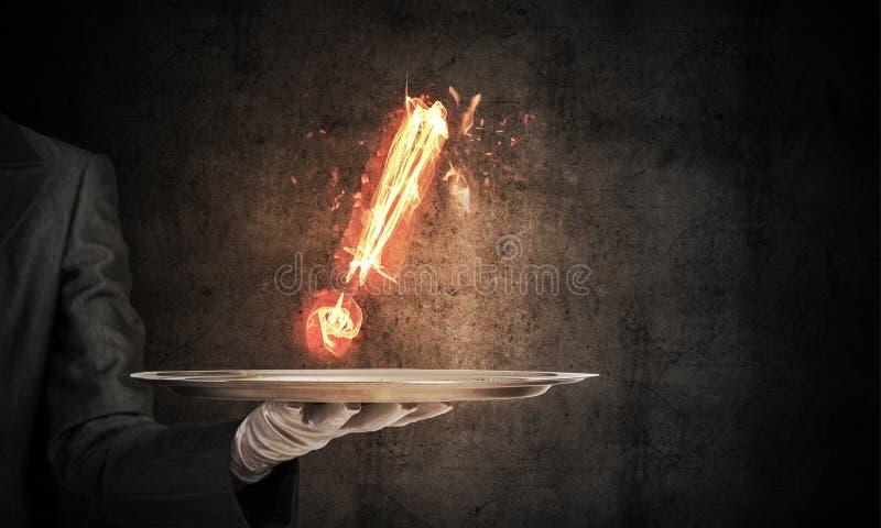 Mão do ` s da empregada de mesa que mantém marca de exclamação flamejante fotografia de stock