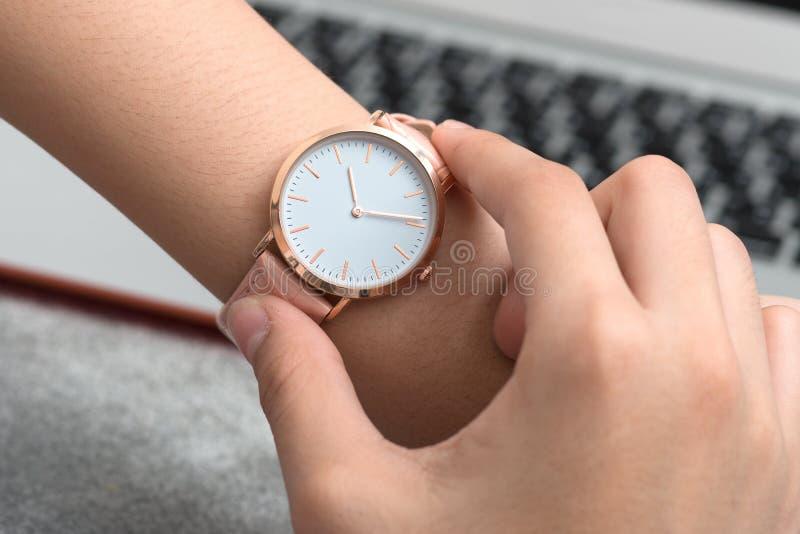 Mão do ` s da menina com o relógio de pulso na frente do laptop imagem de stock