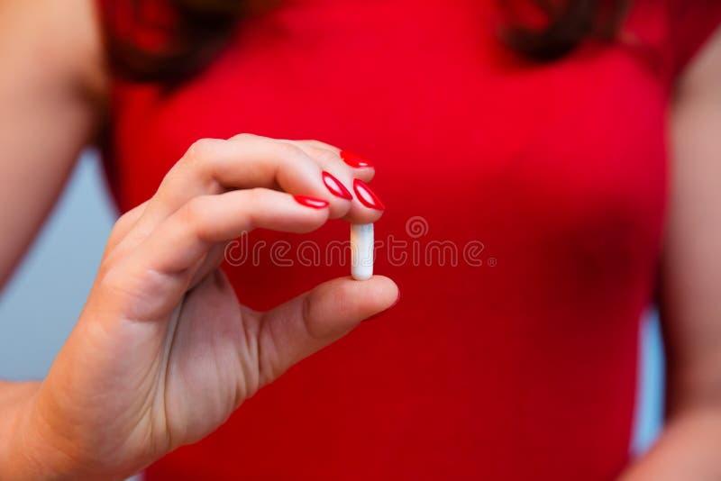 Mão do ` s da mulher com o tratamento de mãos vermelho que guarda o comprimido da vitamina imagens de stock royalty free