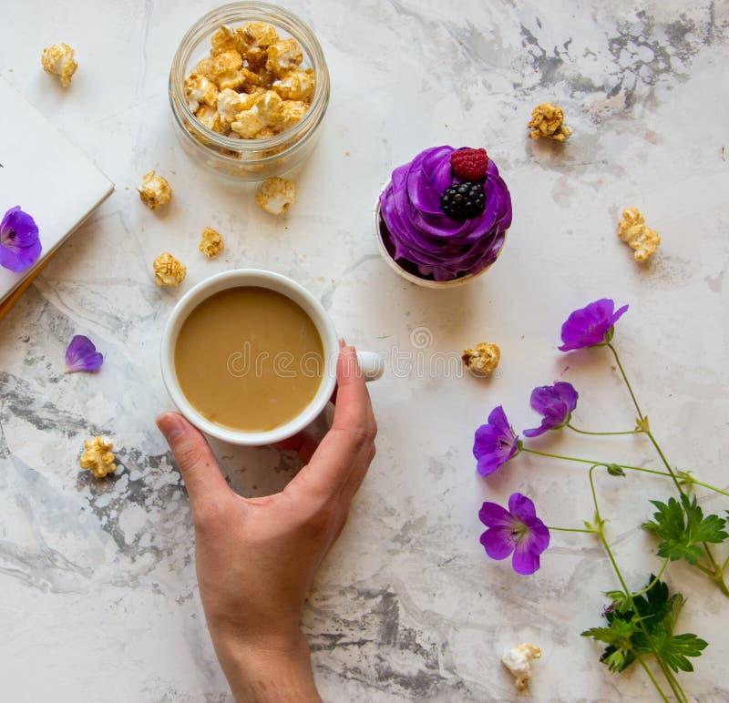 Mão do ` s da mulher com xícara de café, pipoca, as flores selvagens e o viole imagens de stock