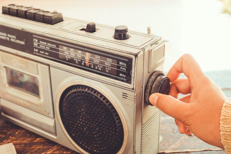 A mão do ` s da mulher comutada e que ajustam o leitor de cassetes do botão e o registrador para escutam música foto de stock royalty free