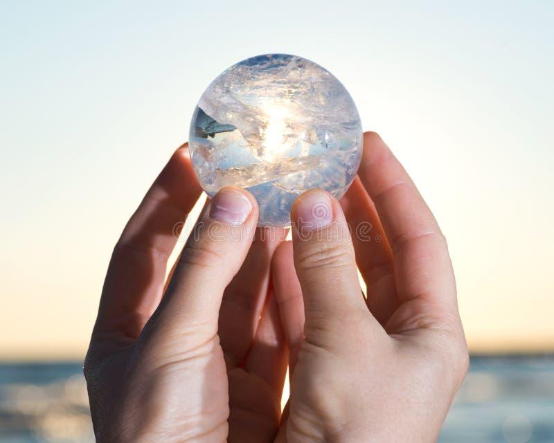 Mão do ` s da mulher que guarda a esfera clara de quartzo de Lemurian no nascer do sol foto de stock royalty free