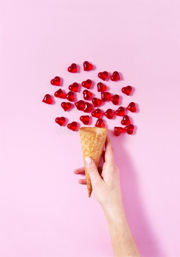 Mão do ` s da mulher que guarda uma colher do gelado A forma do coração deixa cair tudo em torno do gelado da imitação imagem de stock