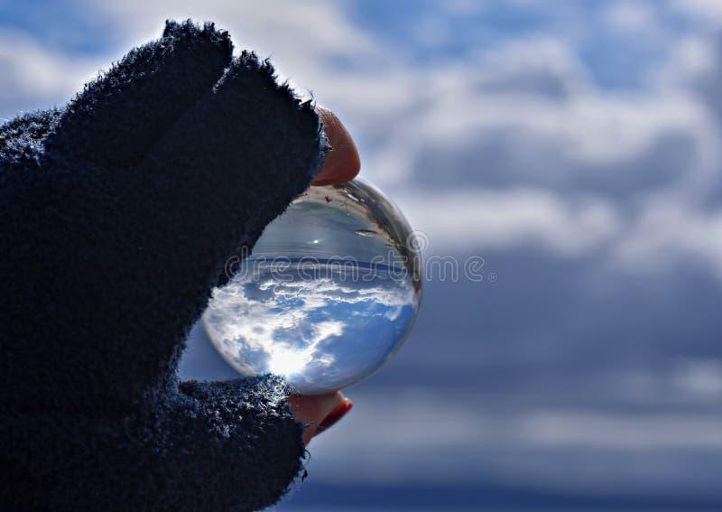 Mão do ` s da mulher que guarda a vista panorâmica do whit da bola de vidro do conceito do mar e do céu para o ambiente imagens de stock